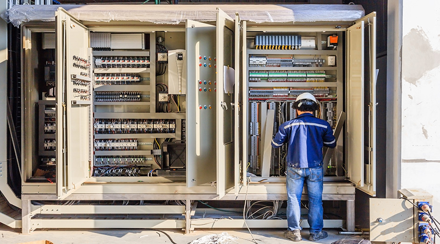 Instrument technician on the job check wiring on PLC cabinet